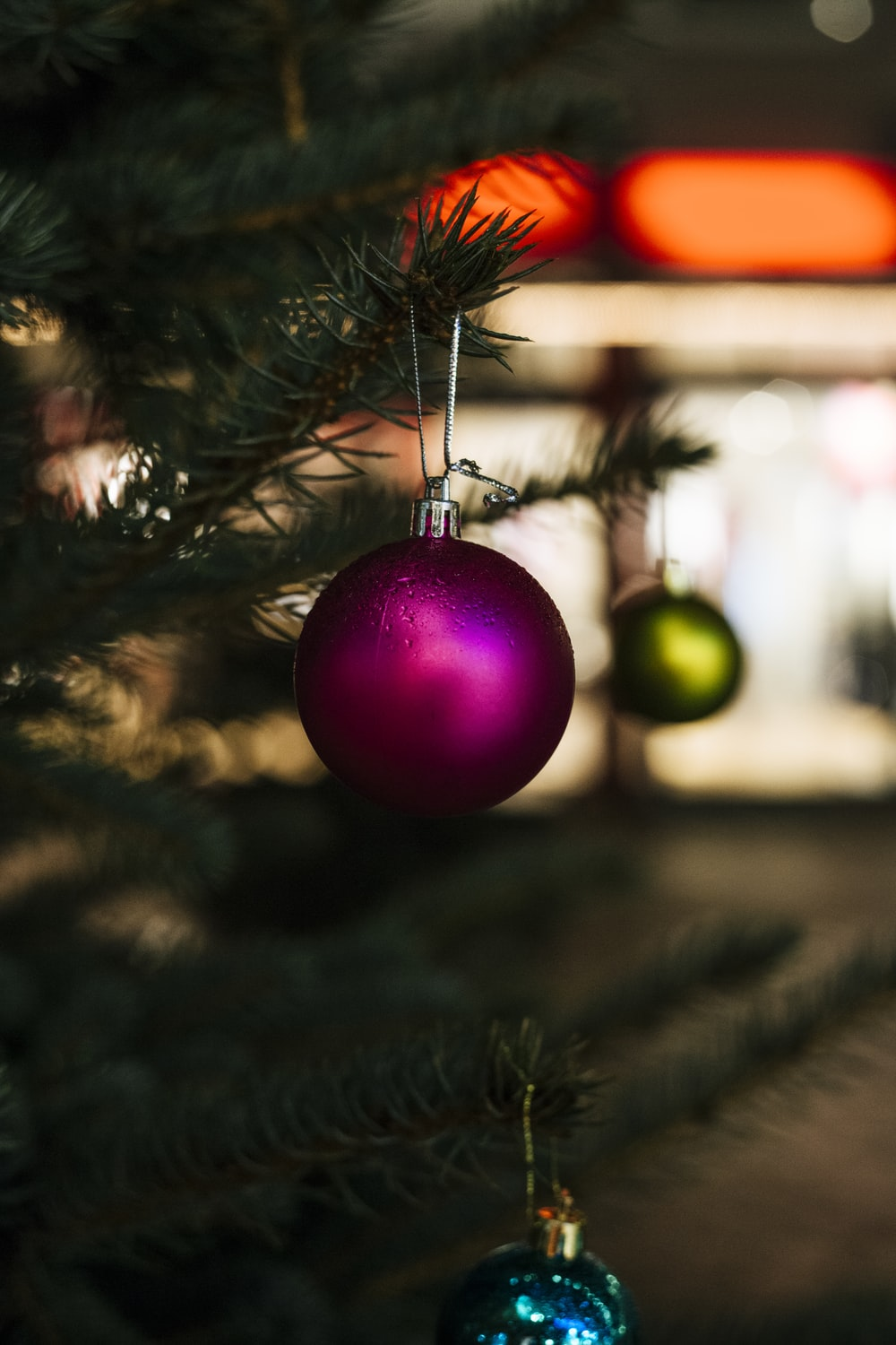 close-up selective focus shot of purple bauble hanging on Christmas tree