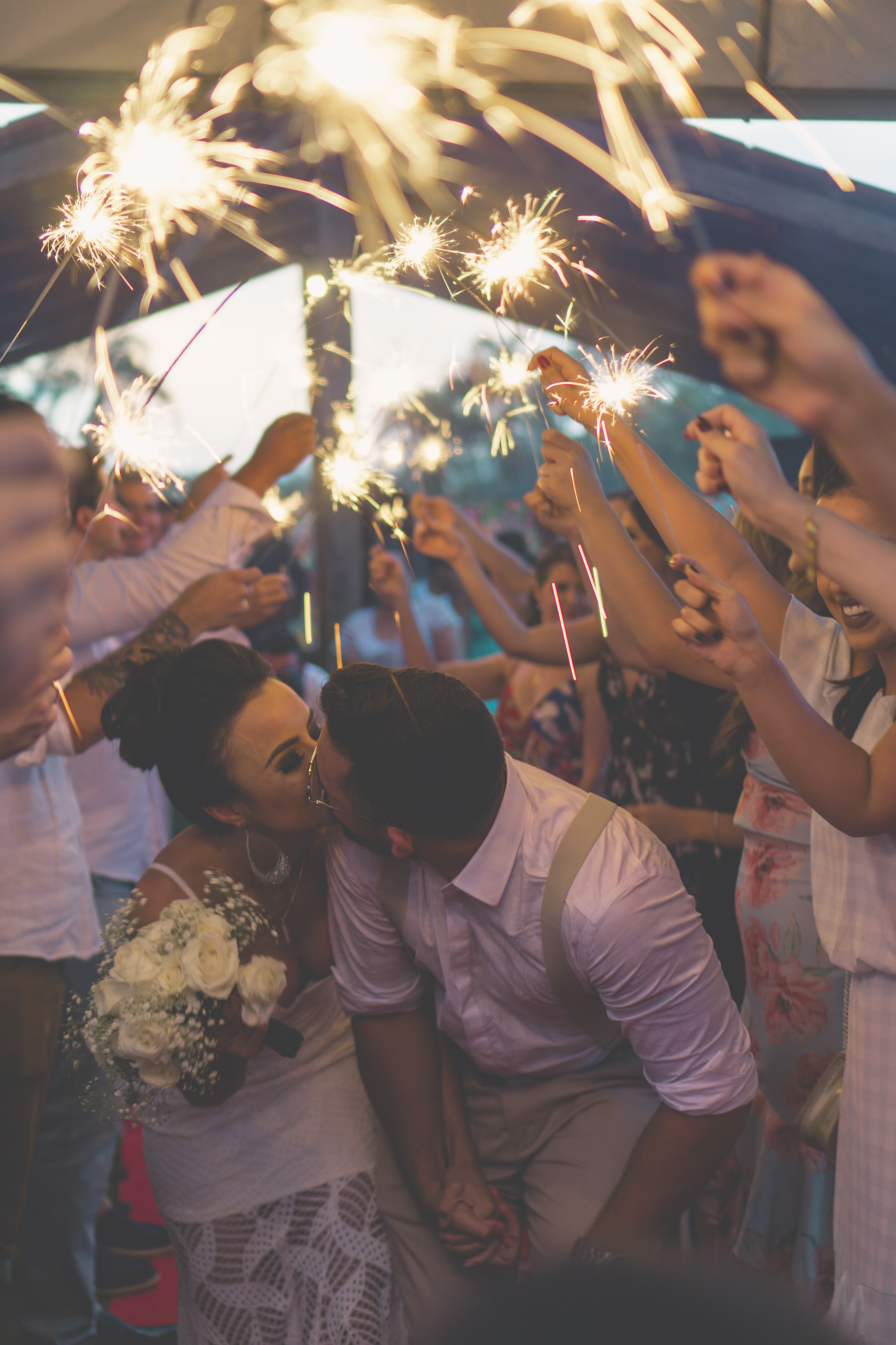 newly wed kissing surrounded by people