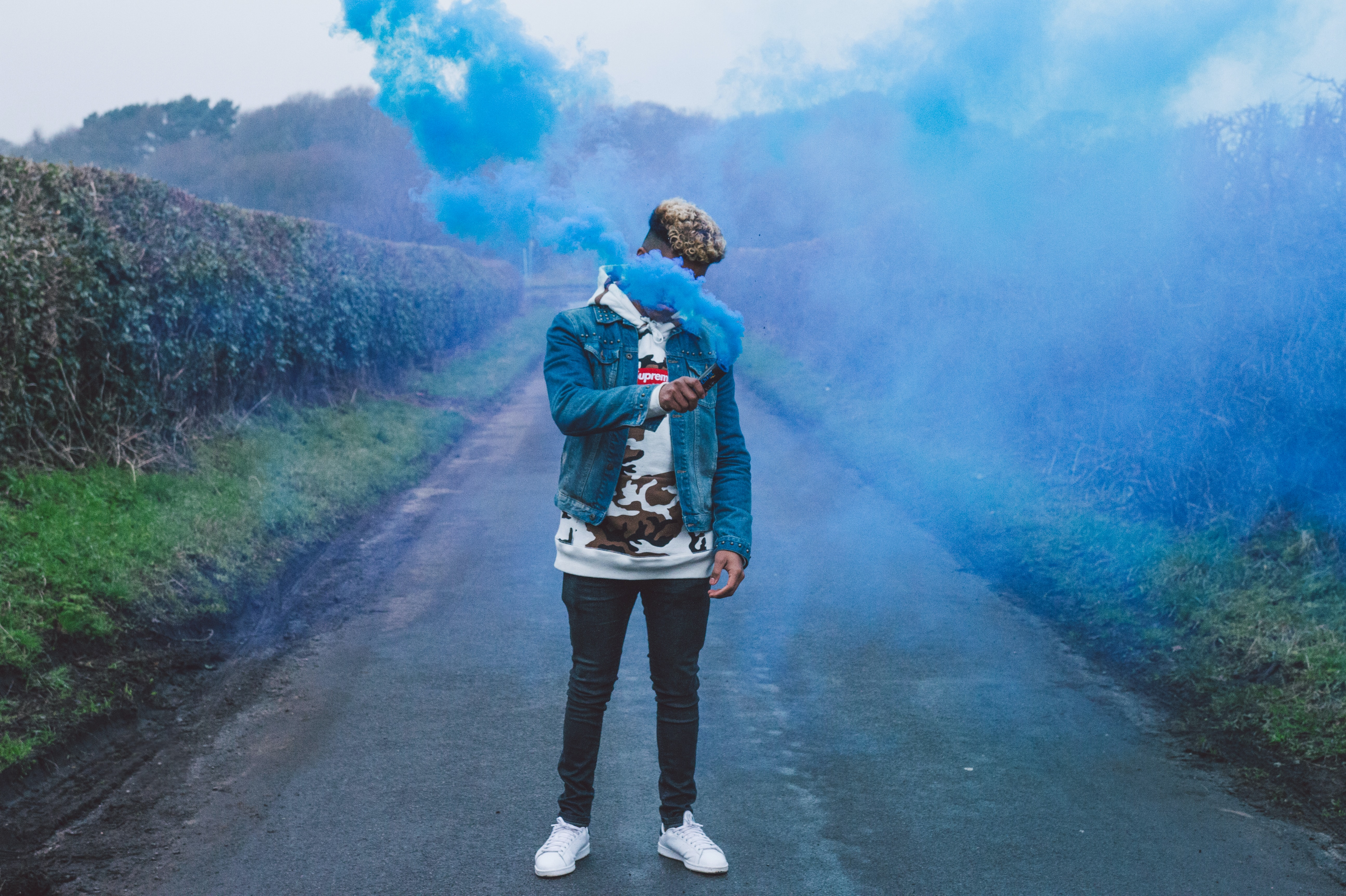 man standing in the middle of footpath holding blue smoke bomb
