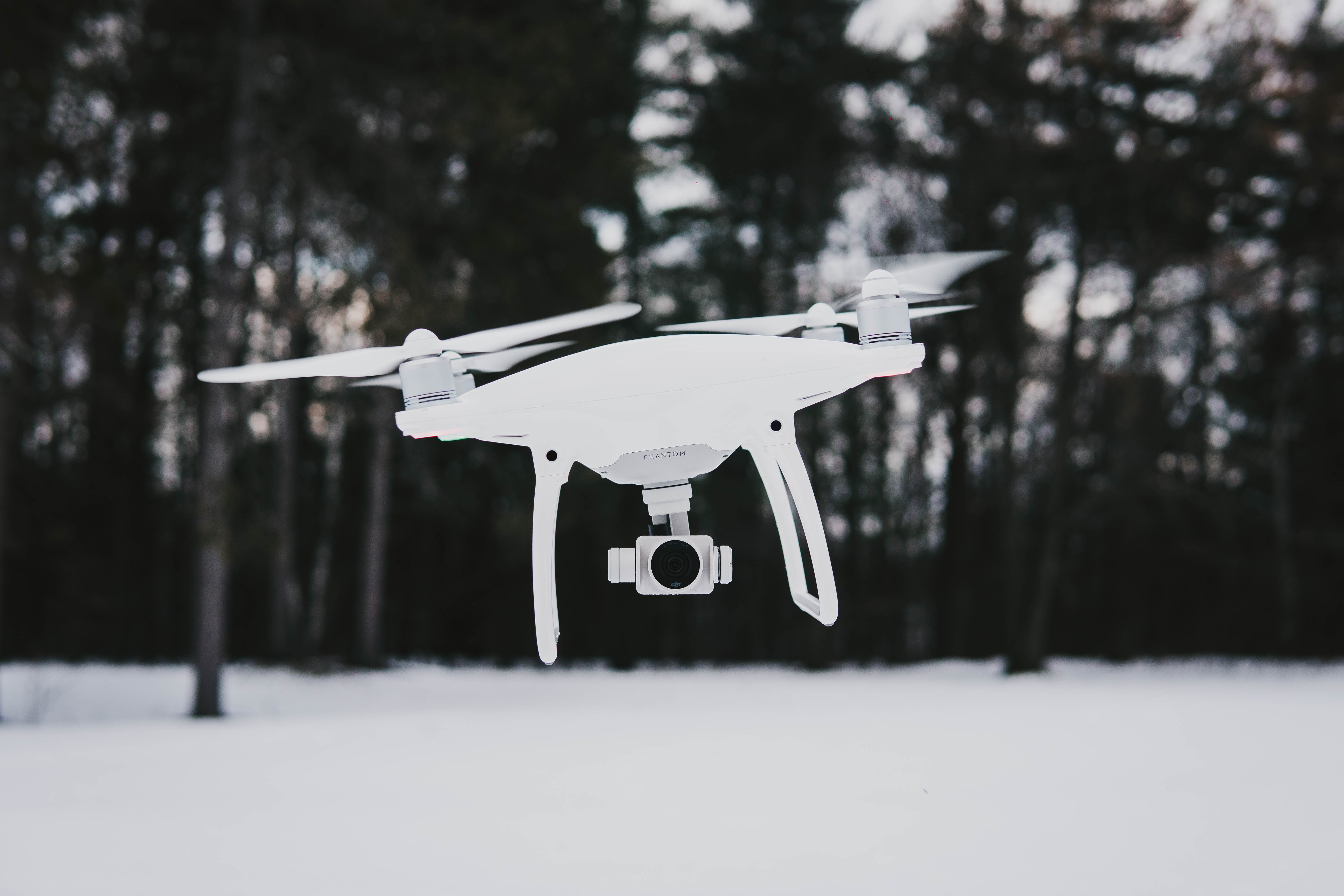 flying quadcopter drone near trees during winter