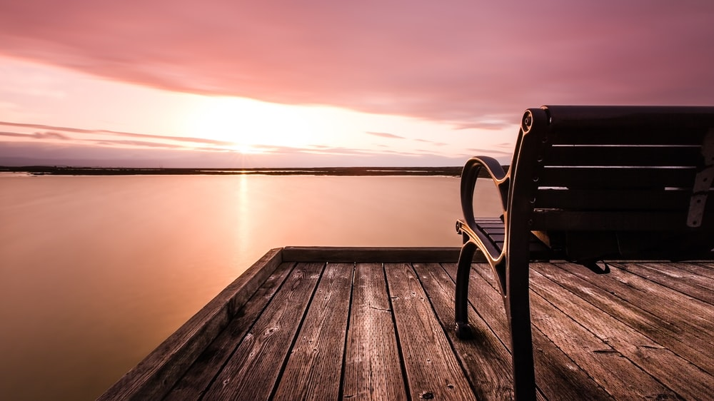 brown bench on wooden dock