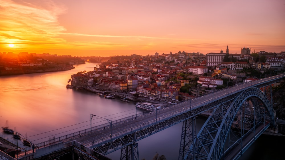 gray bridge near building at sunset