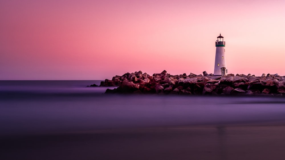 white lighthouse on rocky seashore