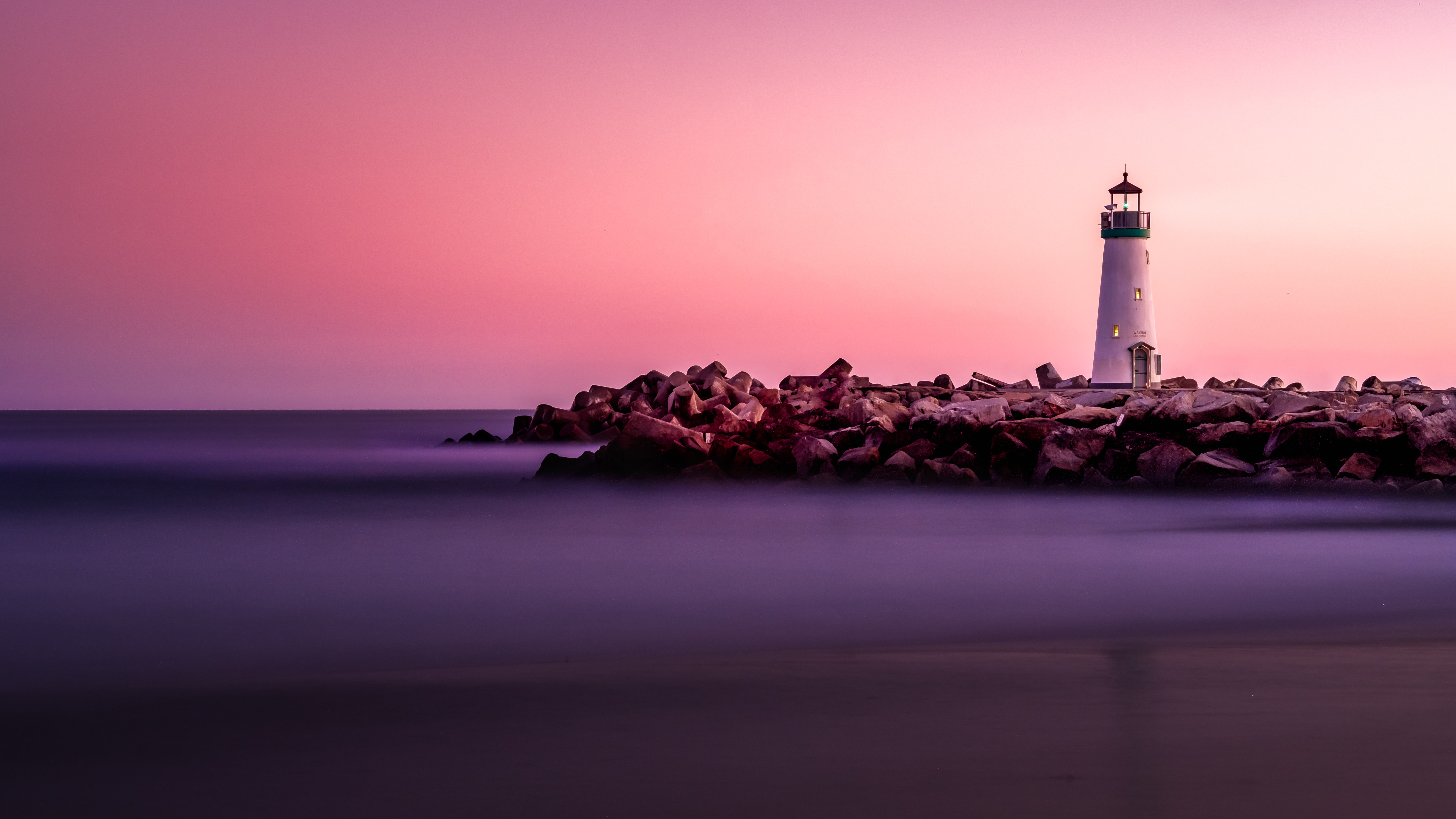 white lighthouse on rocky seashore