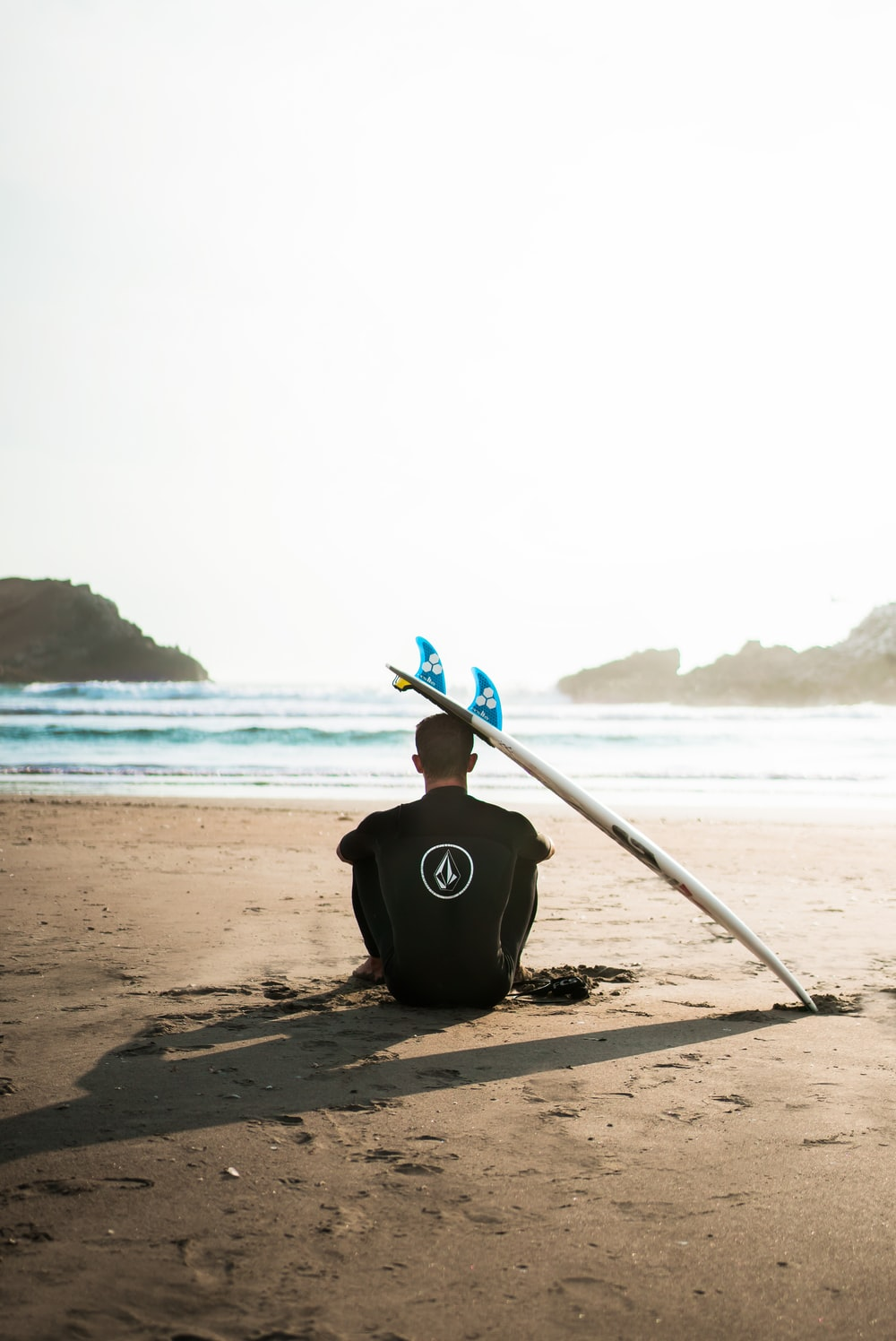man sitting on sand beside surfboard facing sea during daytime