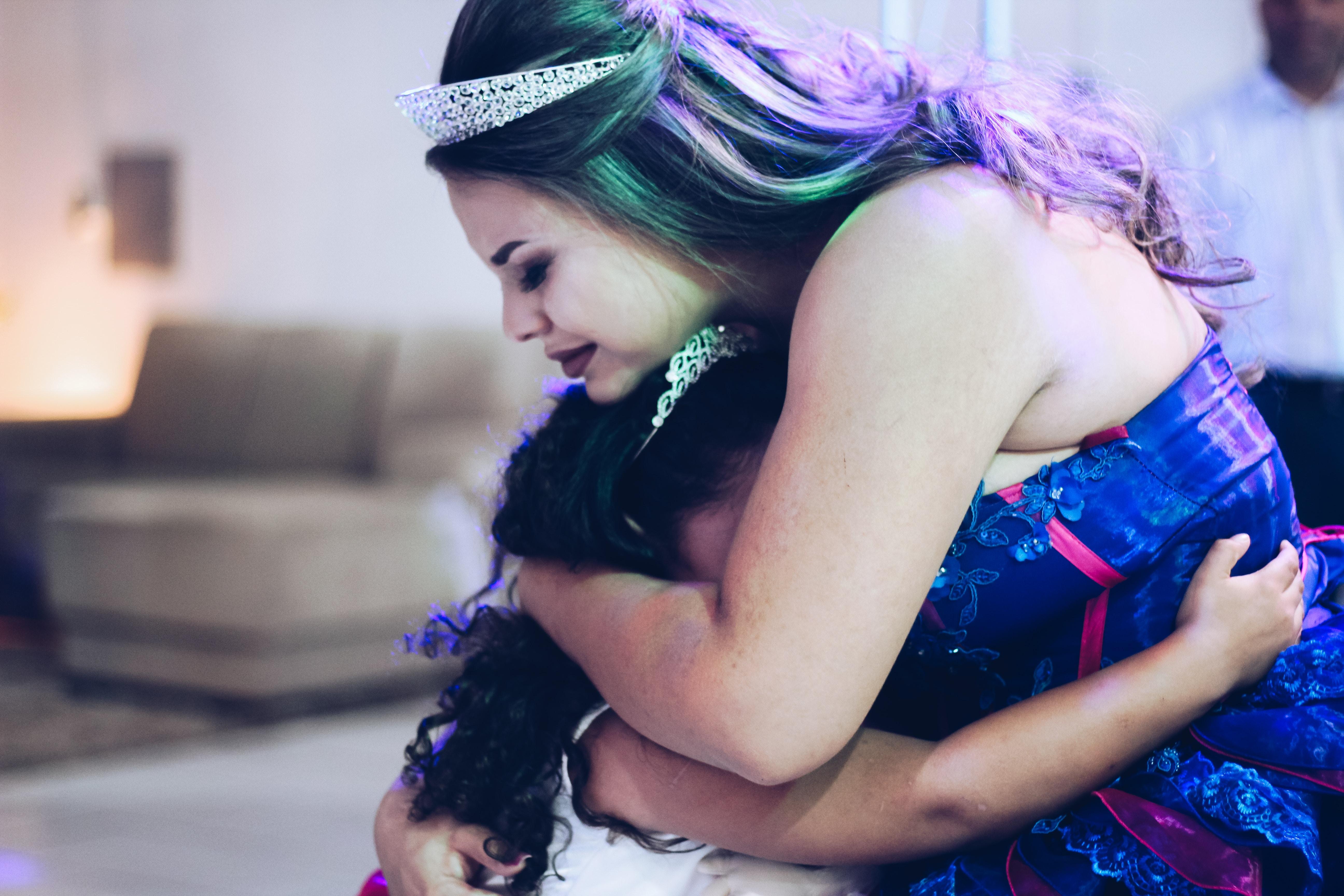 woman hugging girl inside room