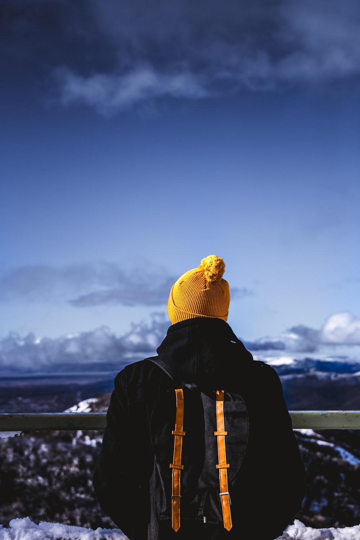 man in black jacket under cloudy blue sky