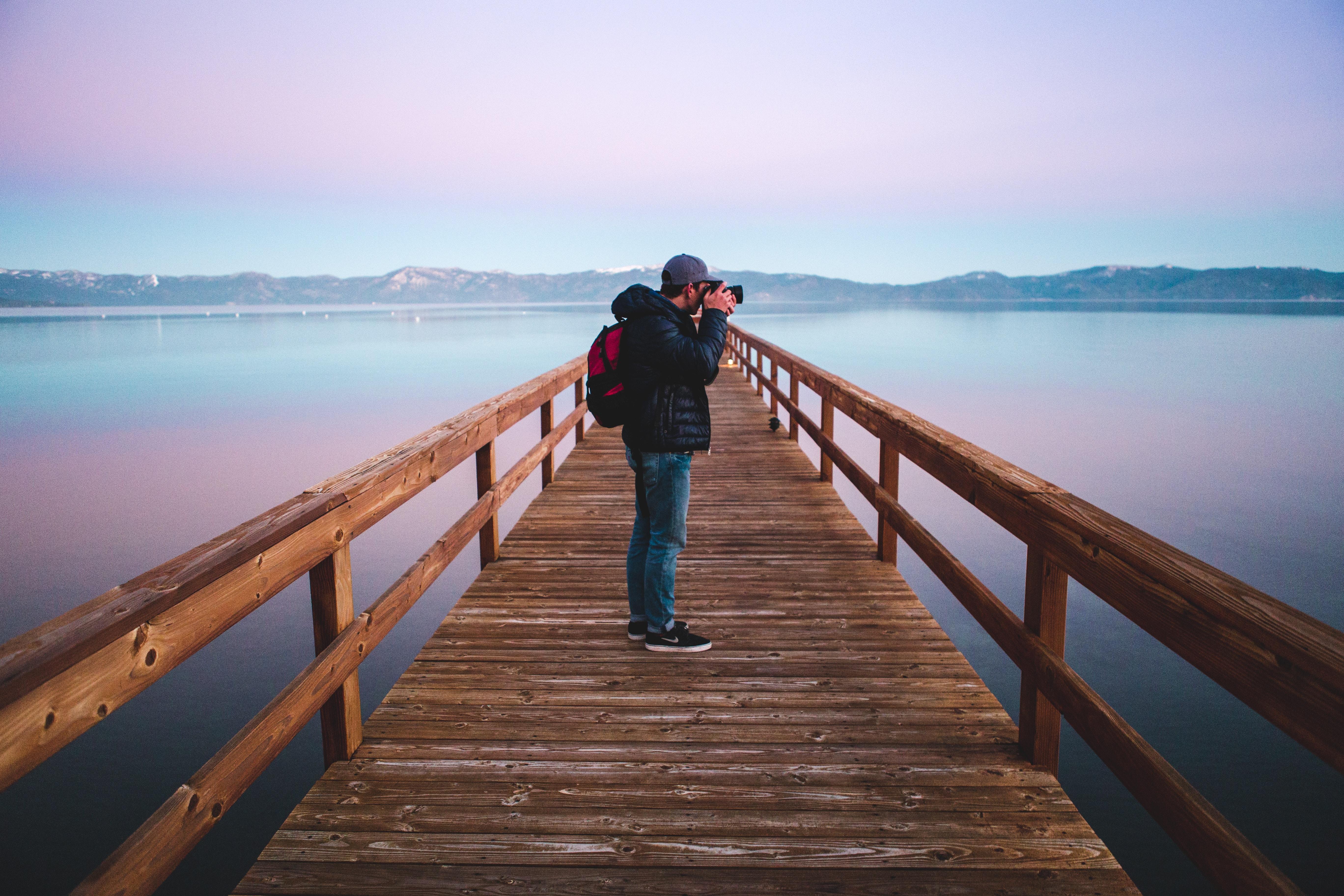 man standing on wood dock taking photo
