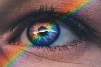 close up photography of rainbow rays on eye eye zoom background