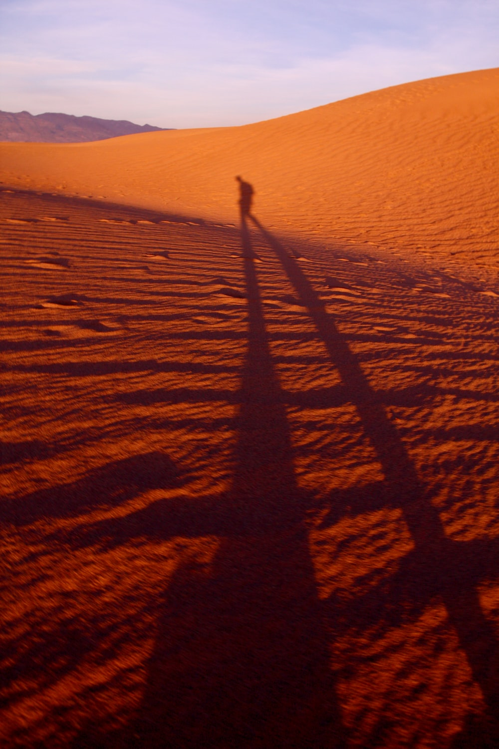 shadow of a person walking on desert