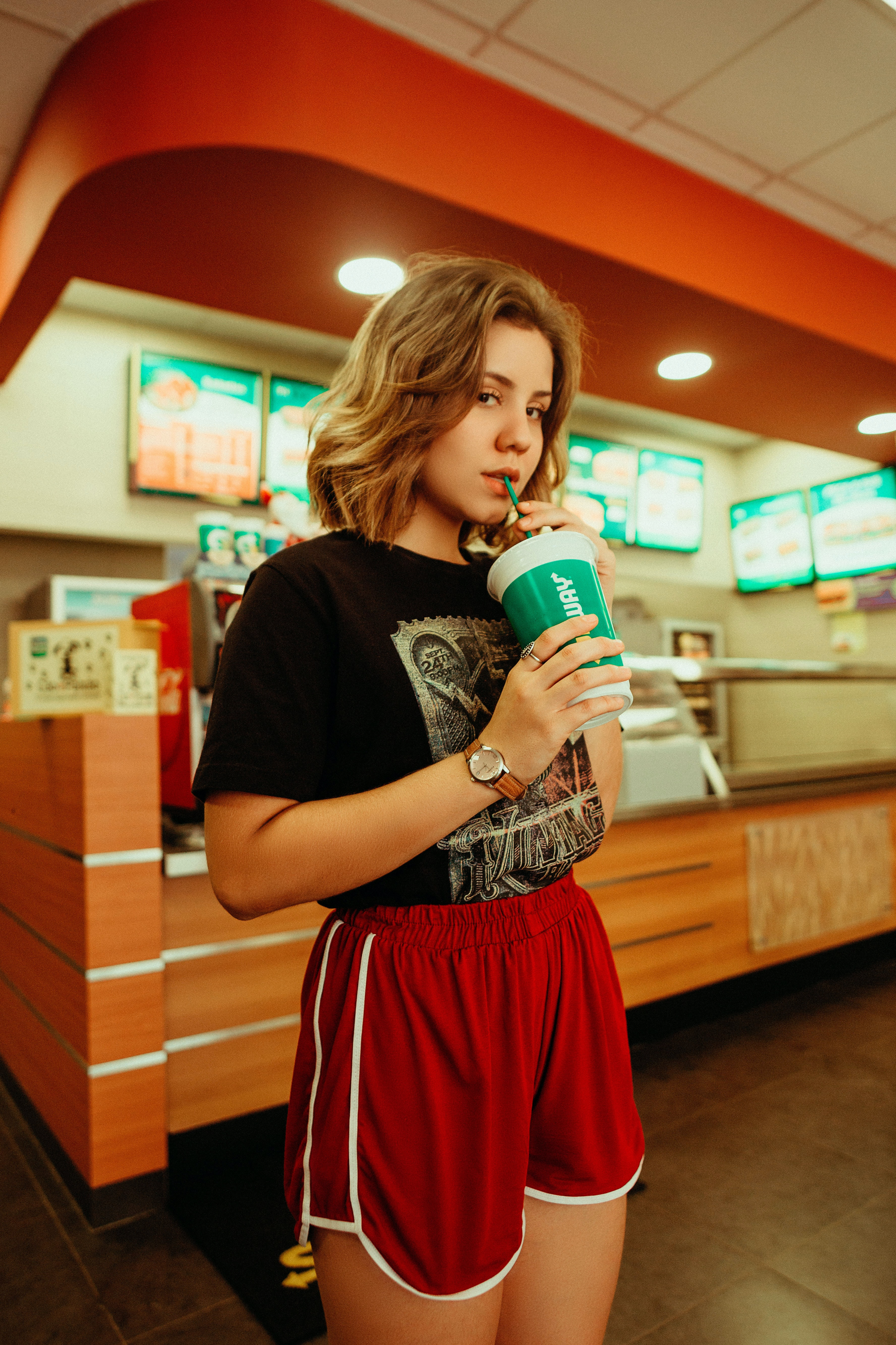 girl drinking plastic cup with straw