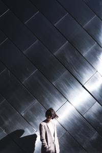 woman standing in-front silver wall
