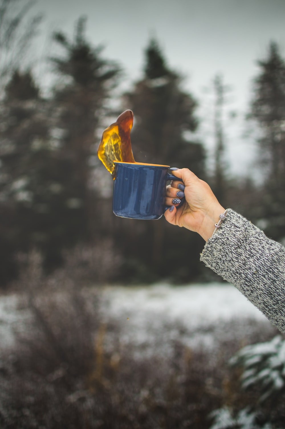 time lapse photo of woman holding blue ceramic mug with coffee spilled upward