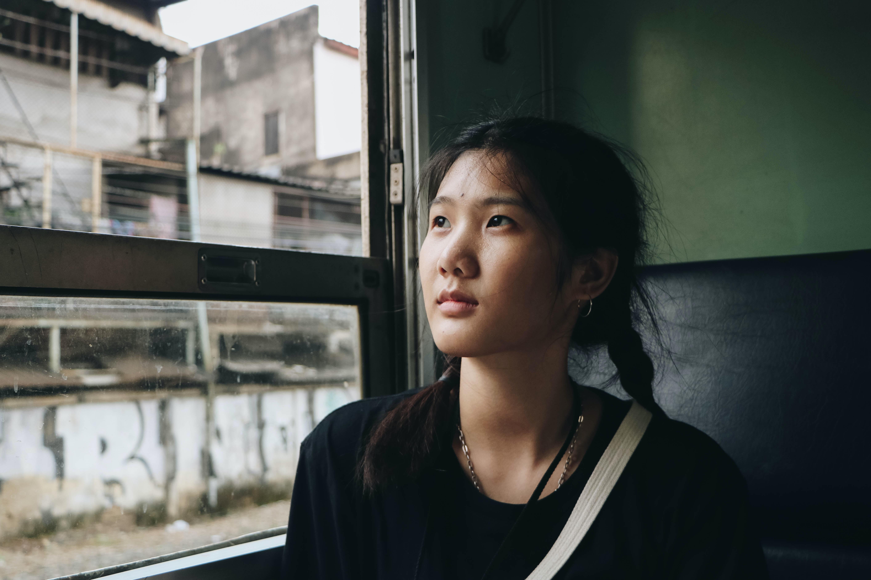woman in black top sitting in vehicle near window