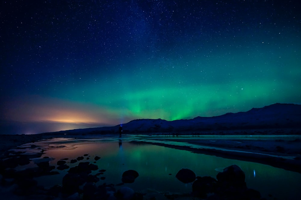 aurora borealis photography of body of water and mountain