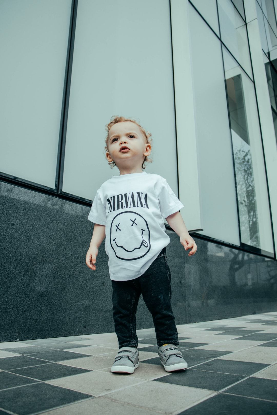 child in Nirvana shirt standing near building