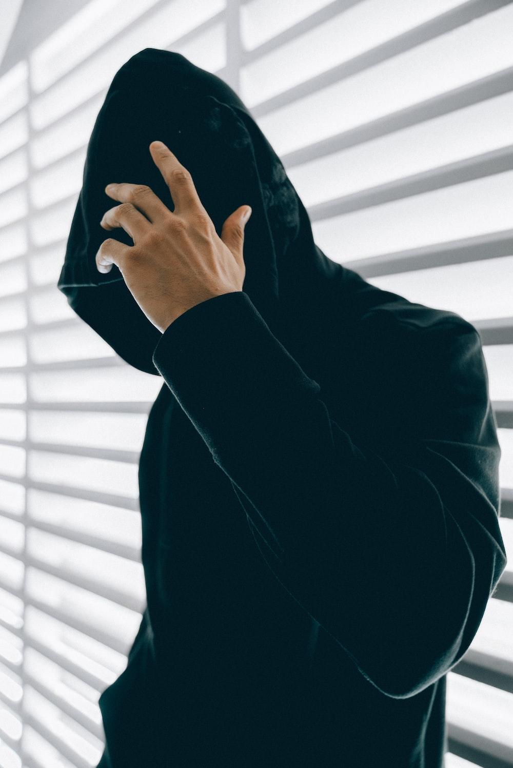 person wearing green hooded jacket inside room