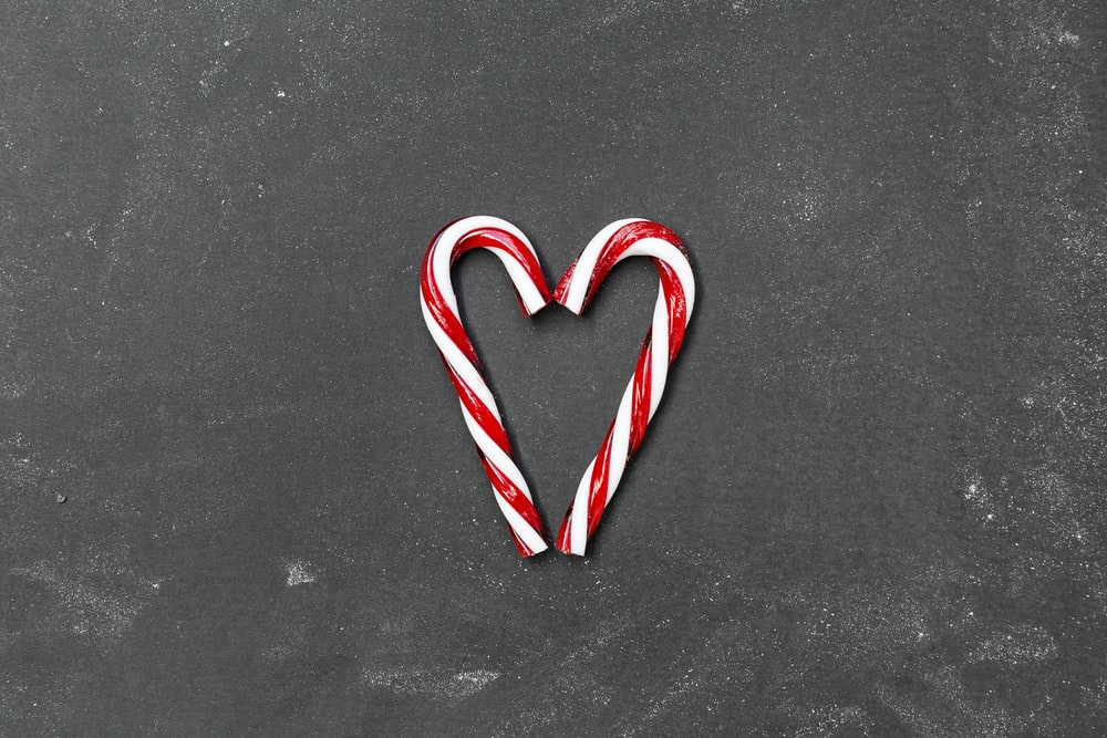 two red-and-white candy canes on gray surface