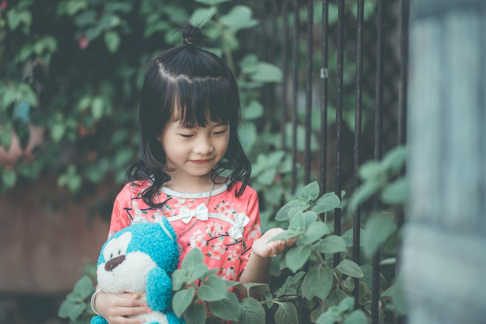 toddler girl holding leaf and plush toy near fence during daytime
