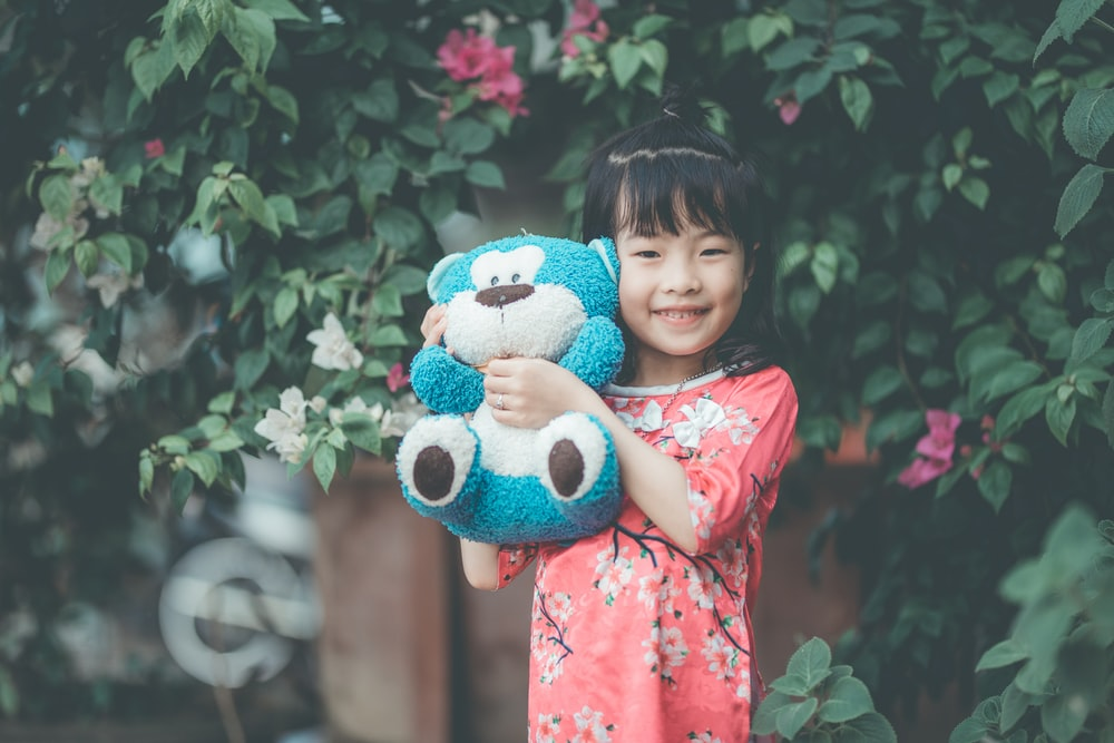 girl holding blue and white plush toy while standing near green plant during daytime