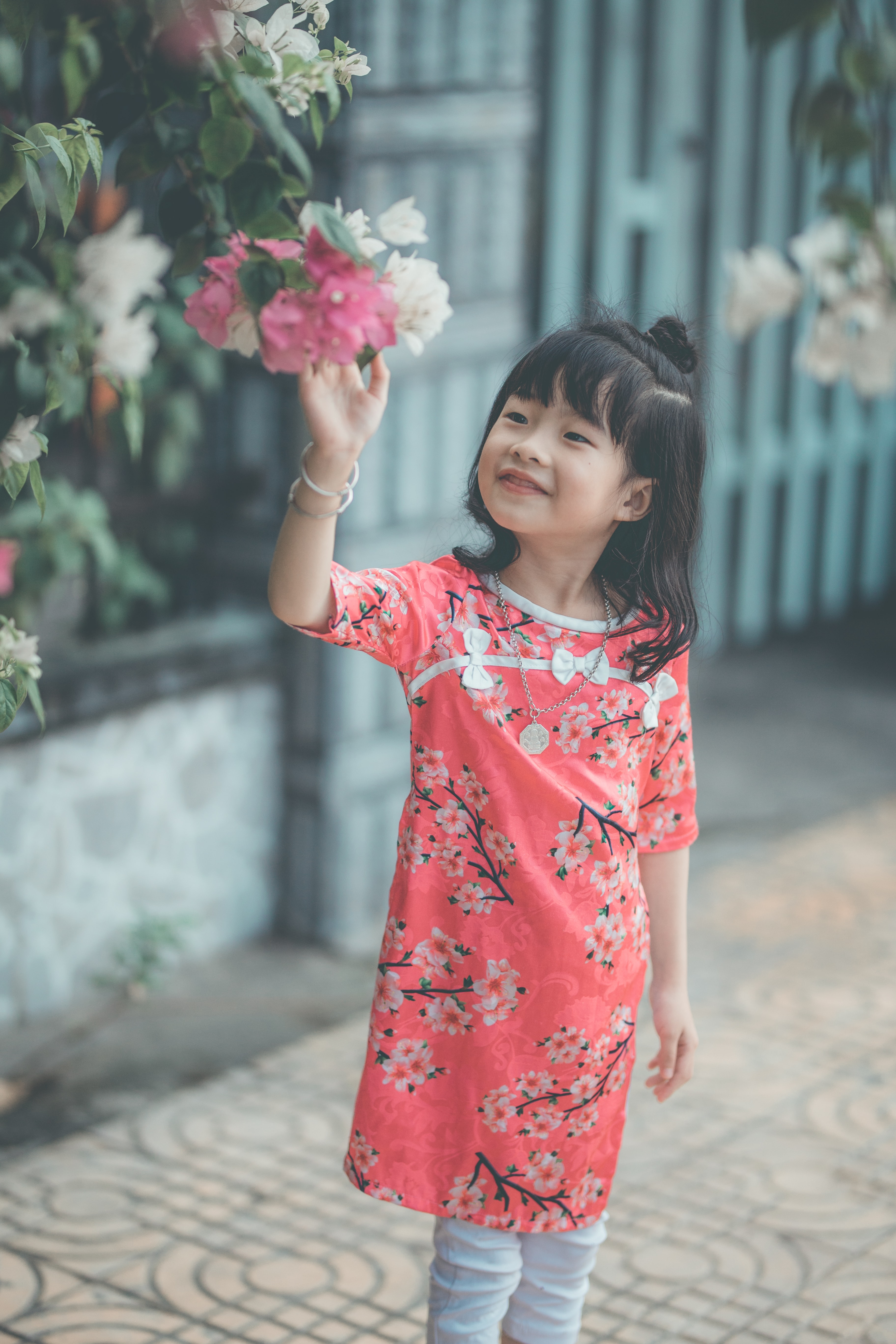 girl standing about to touch flower