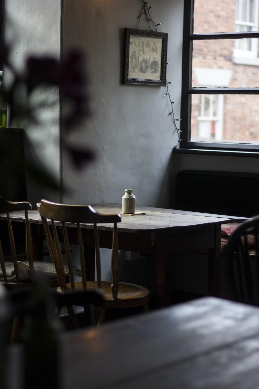 white plastic bottle on brown wooden table near glass window
