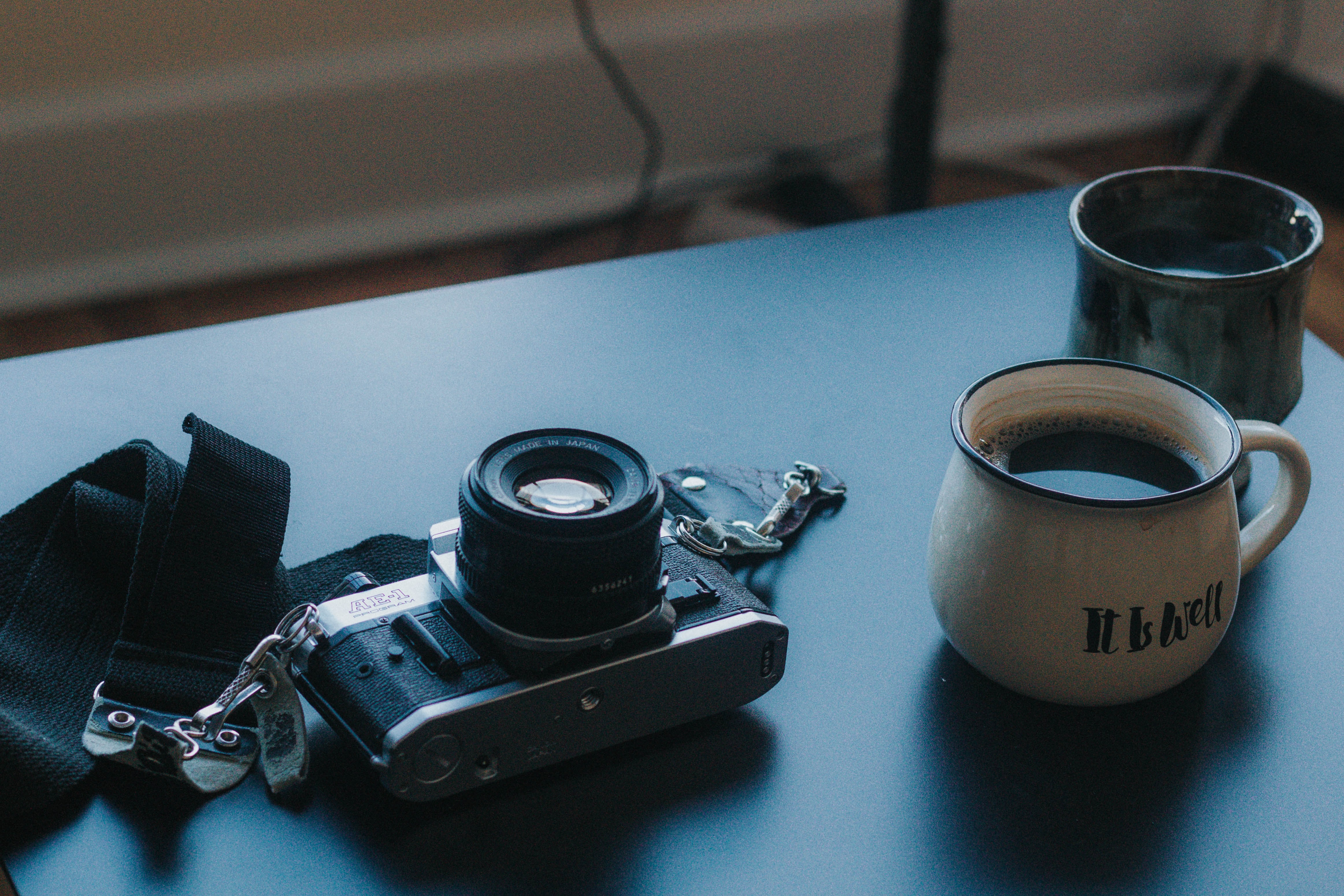 black DSLR camera beside ceramic cup filled with coffee