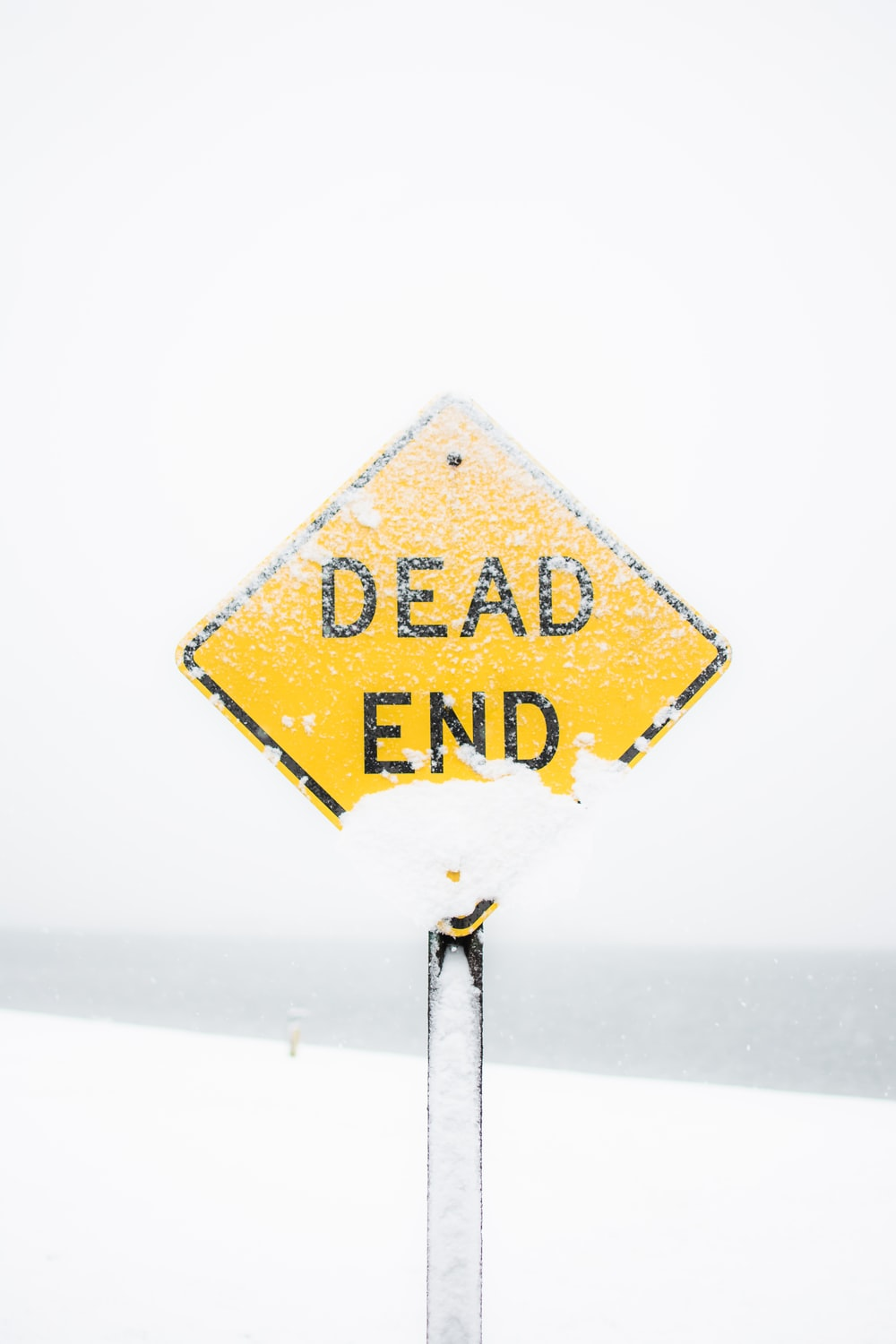 focus photography of dead end road sign covered with snow