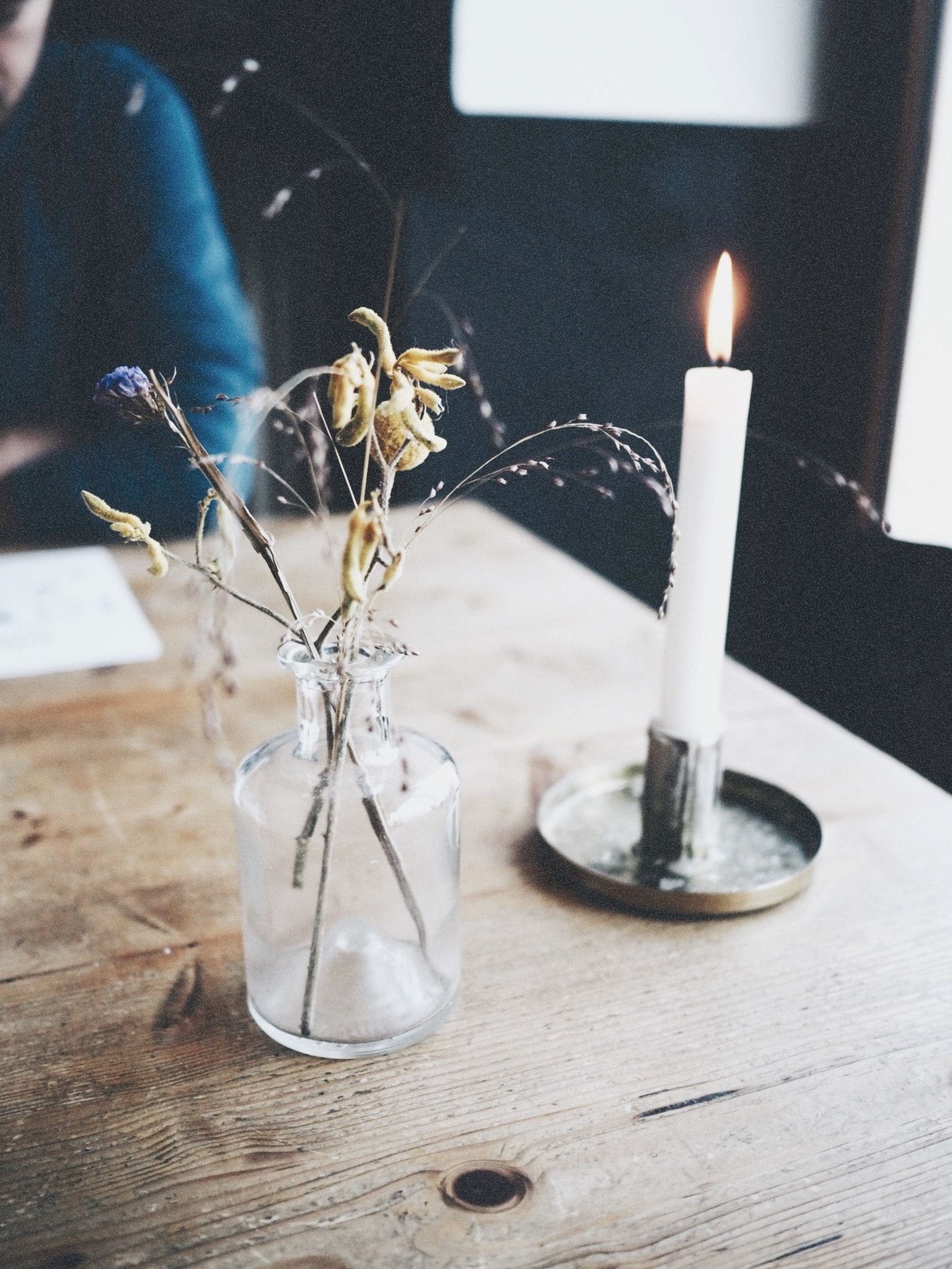 lighted white candle on brown wooden table