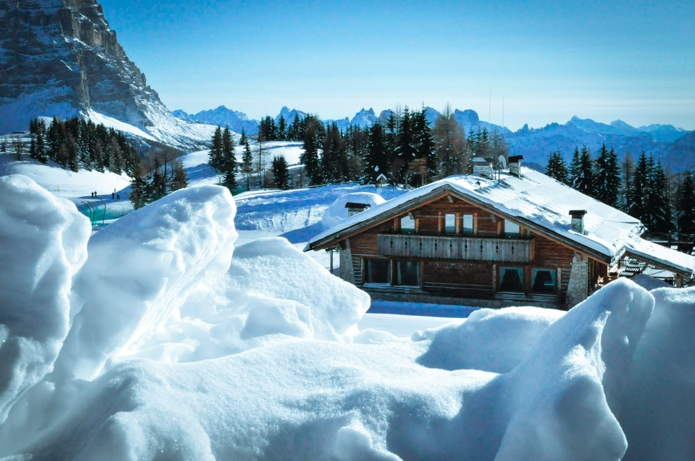 brown house beside mountain with snow
