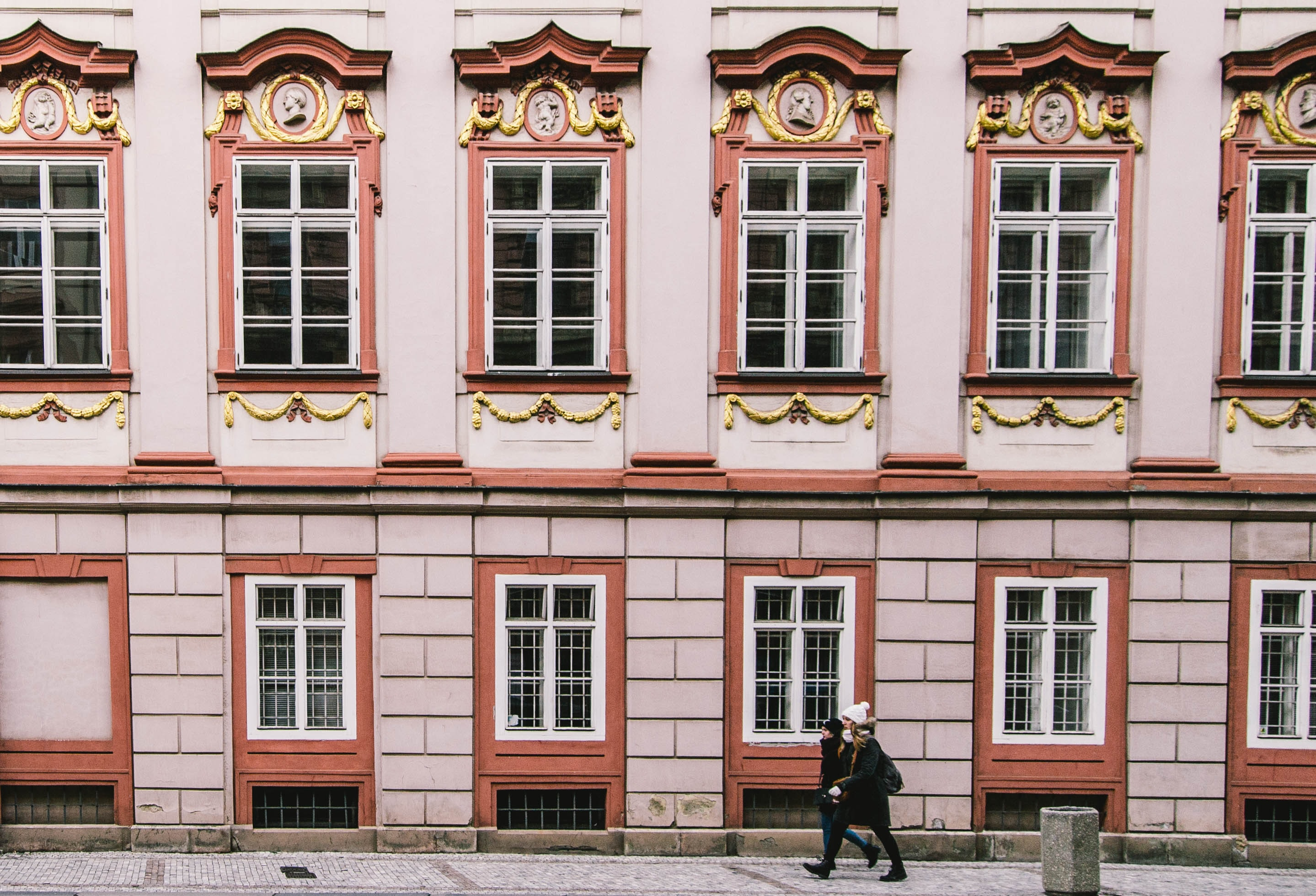 woman walking beside pink building