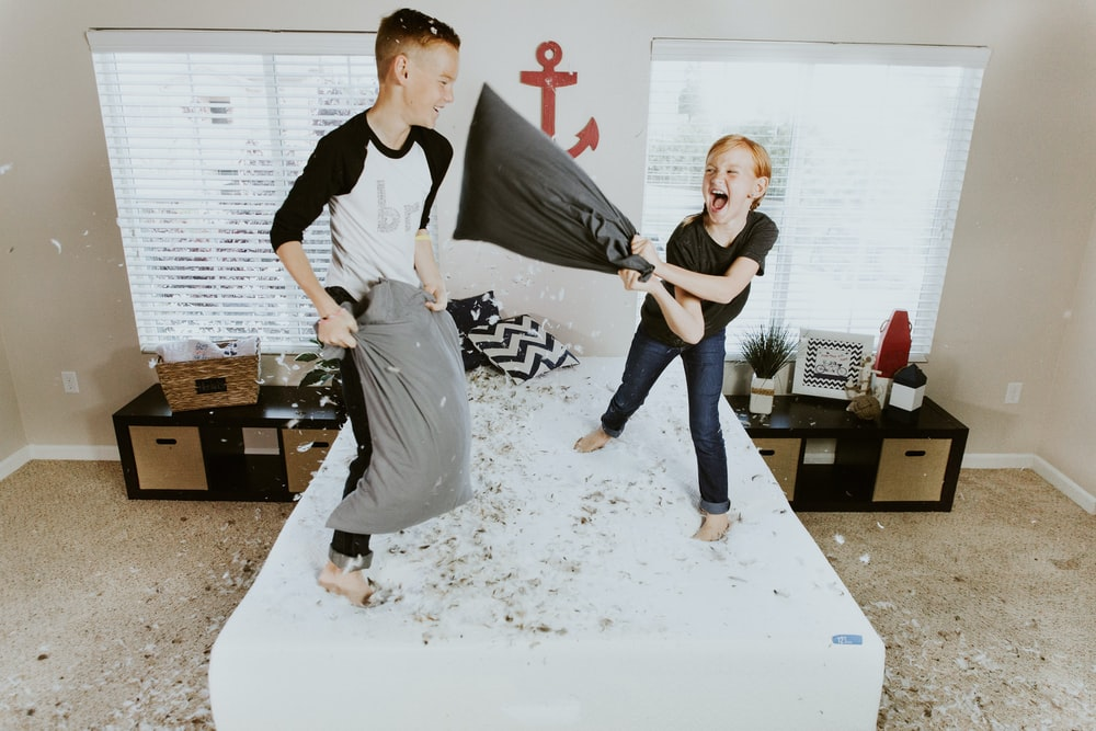 boy and girl having pillow fight