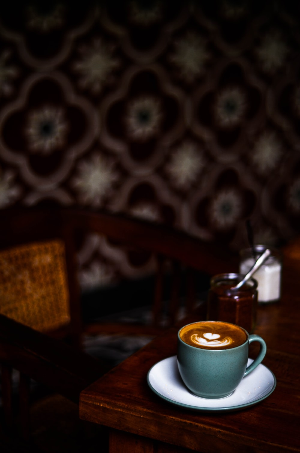 focus photography of coffee cup on sauce on table top