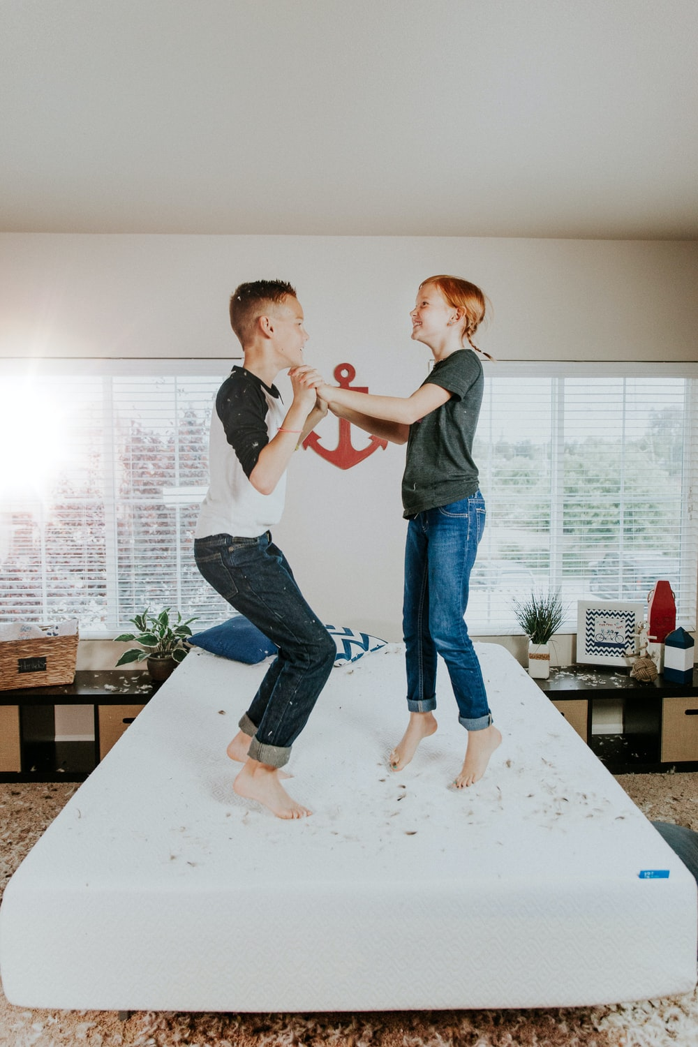 boy and girl jumping on white bed mattress inside room