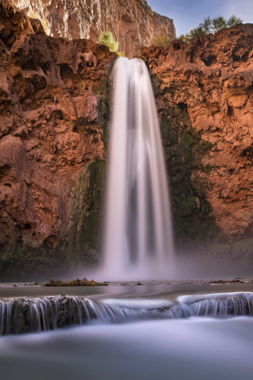 waterfalls between brown rock formation