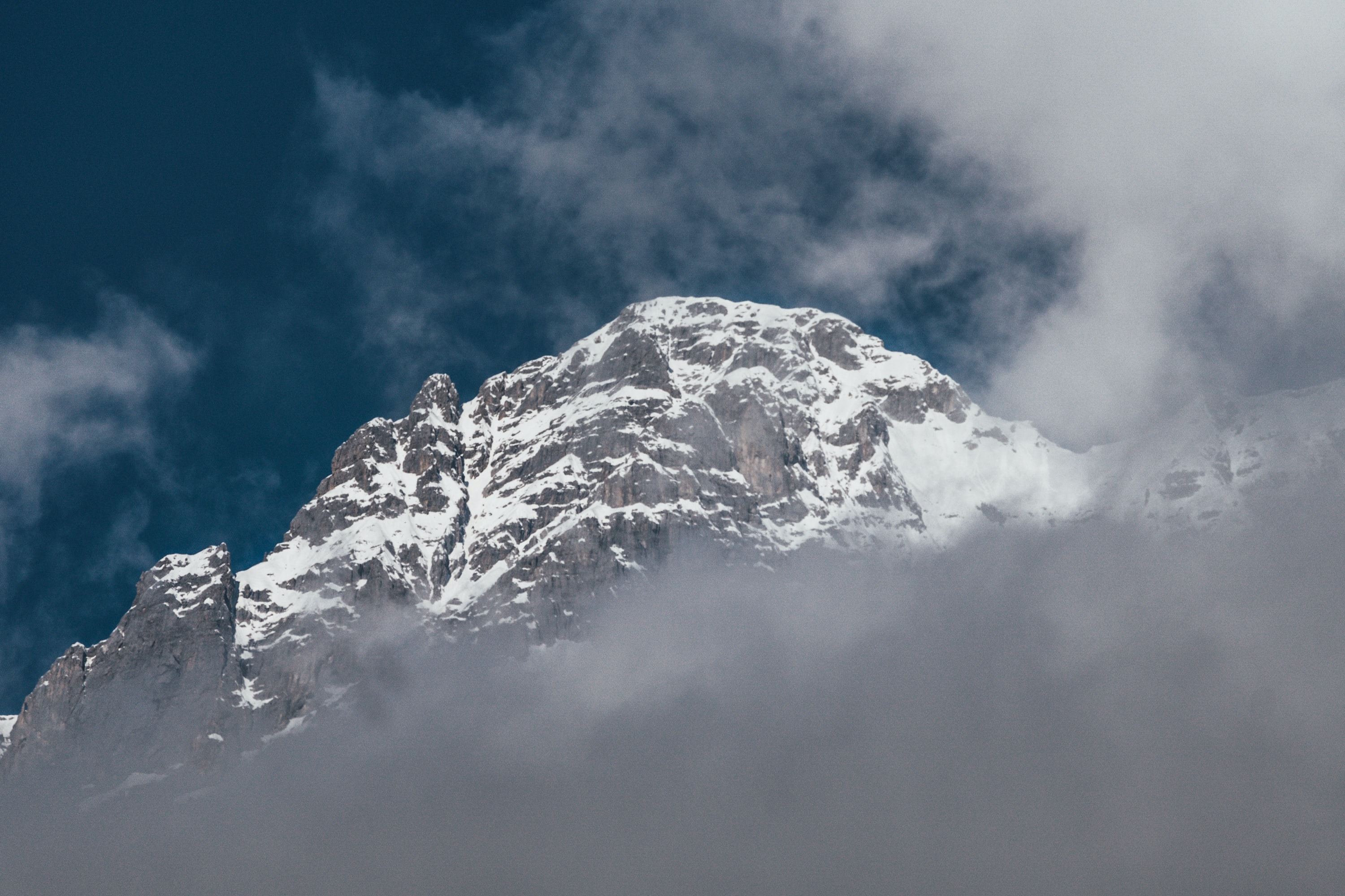 snow covered mountain under blue cloudy sky
