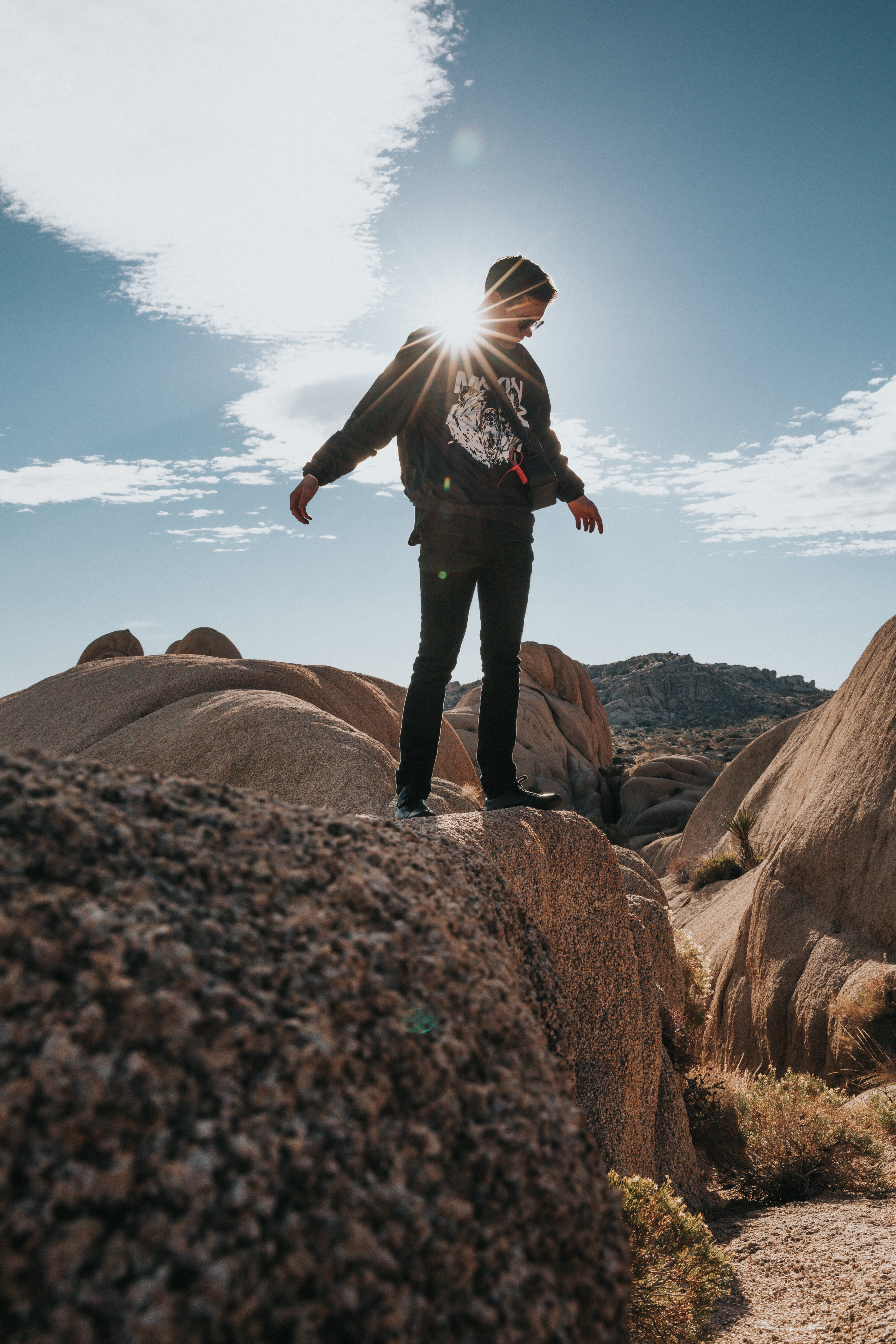 man looking down and standing on elevated rocky surface during daytime