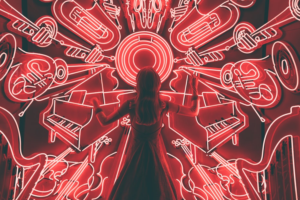 woman standing watching LED light musical instrument
