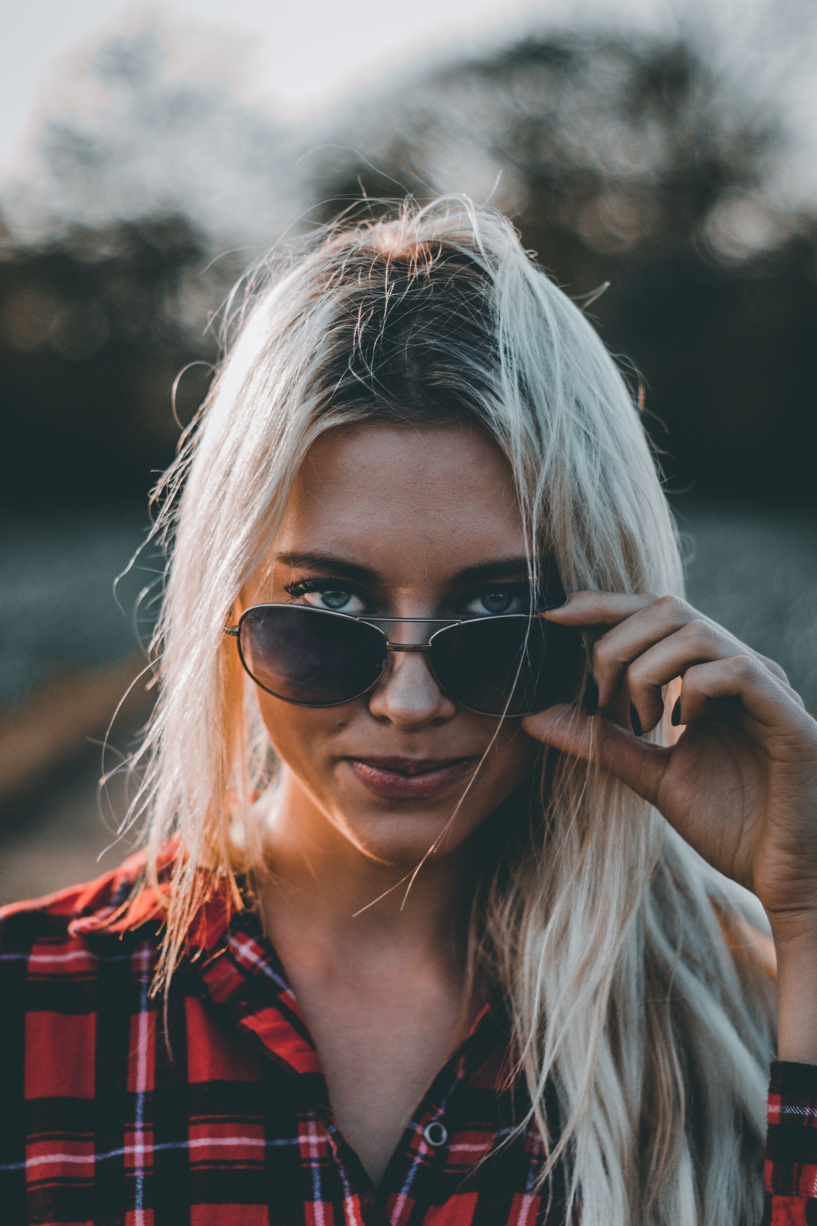 woman wearing red and black plaid top holding sunglasses