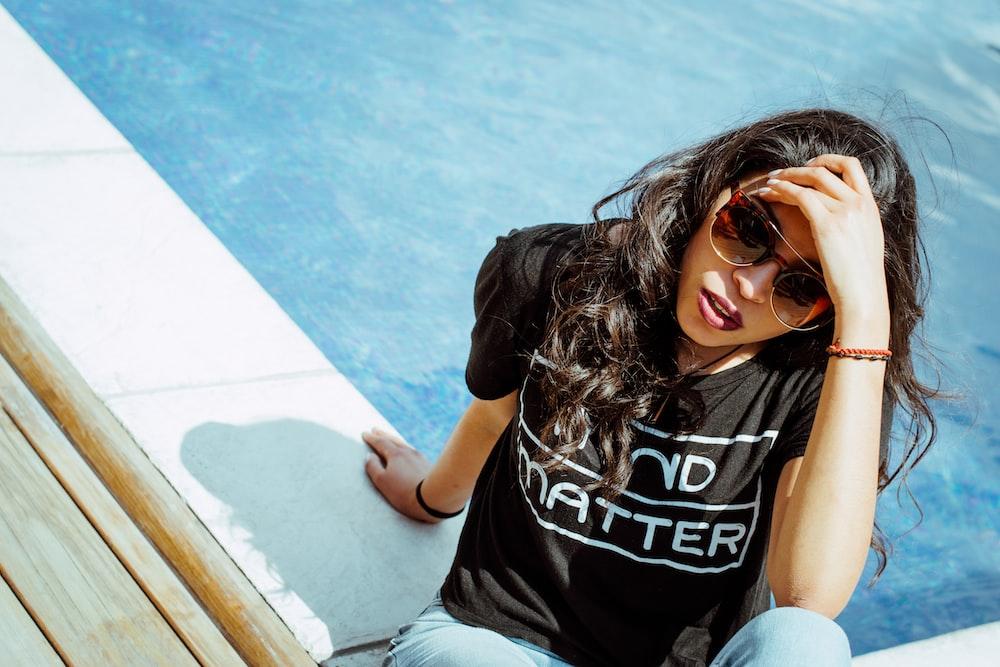 woman in black t-shirt sits near swimming pool