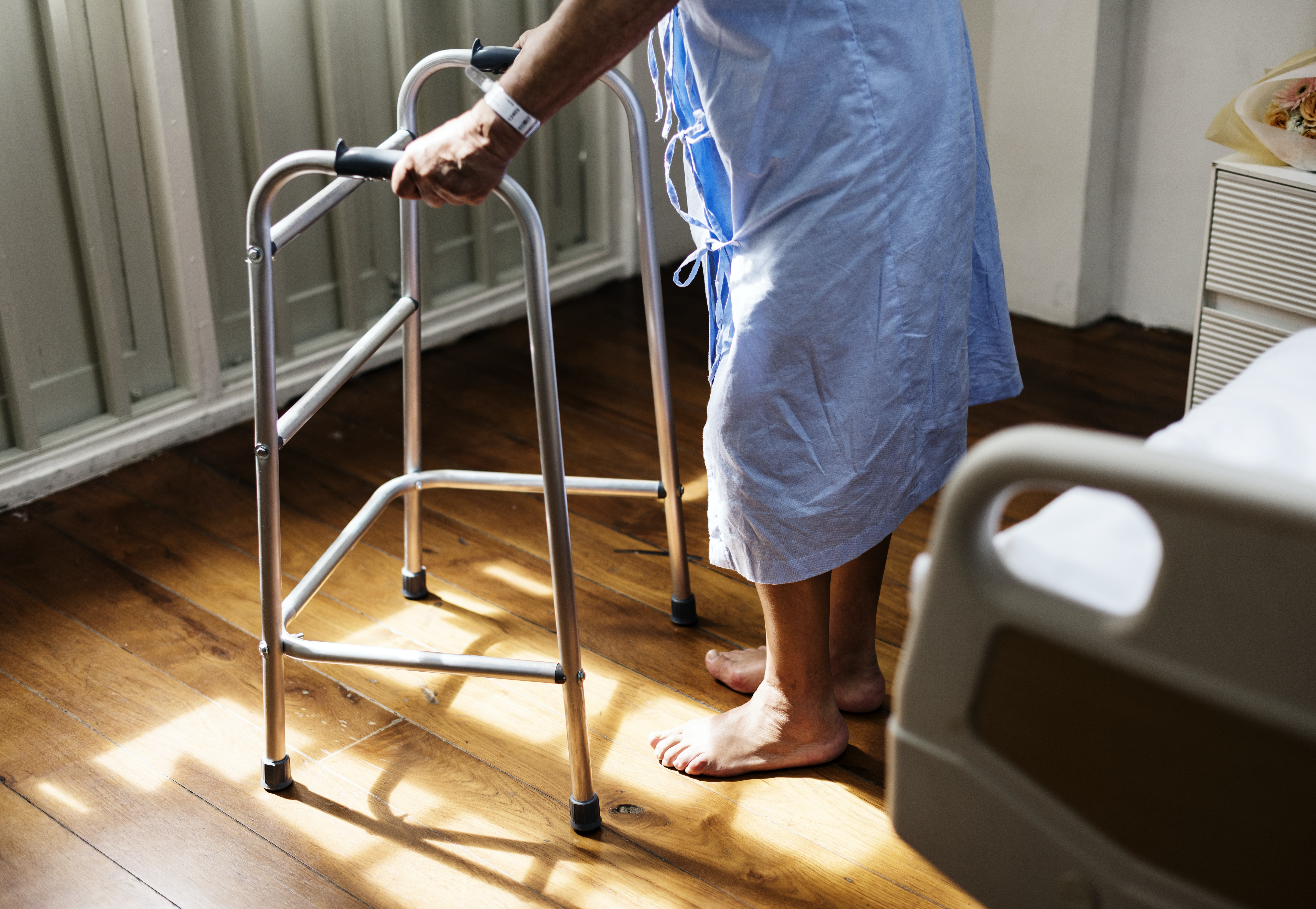 man standing using adult walker inside room