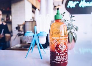 half-filled bottle beside cup rack