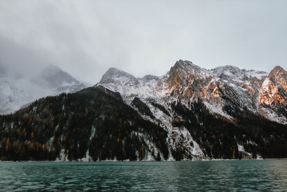 snow capped mountain near body of water