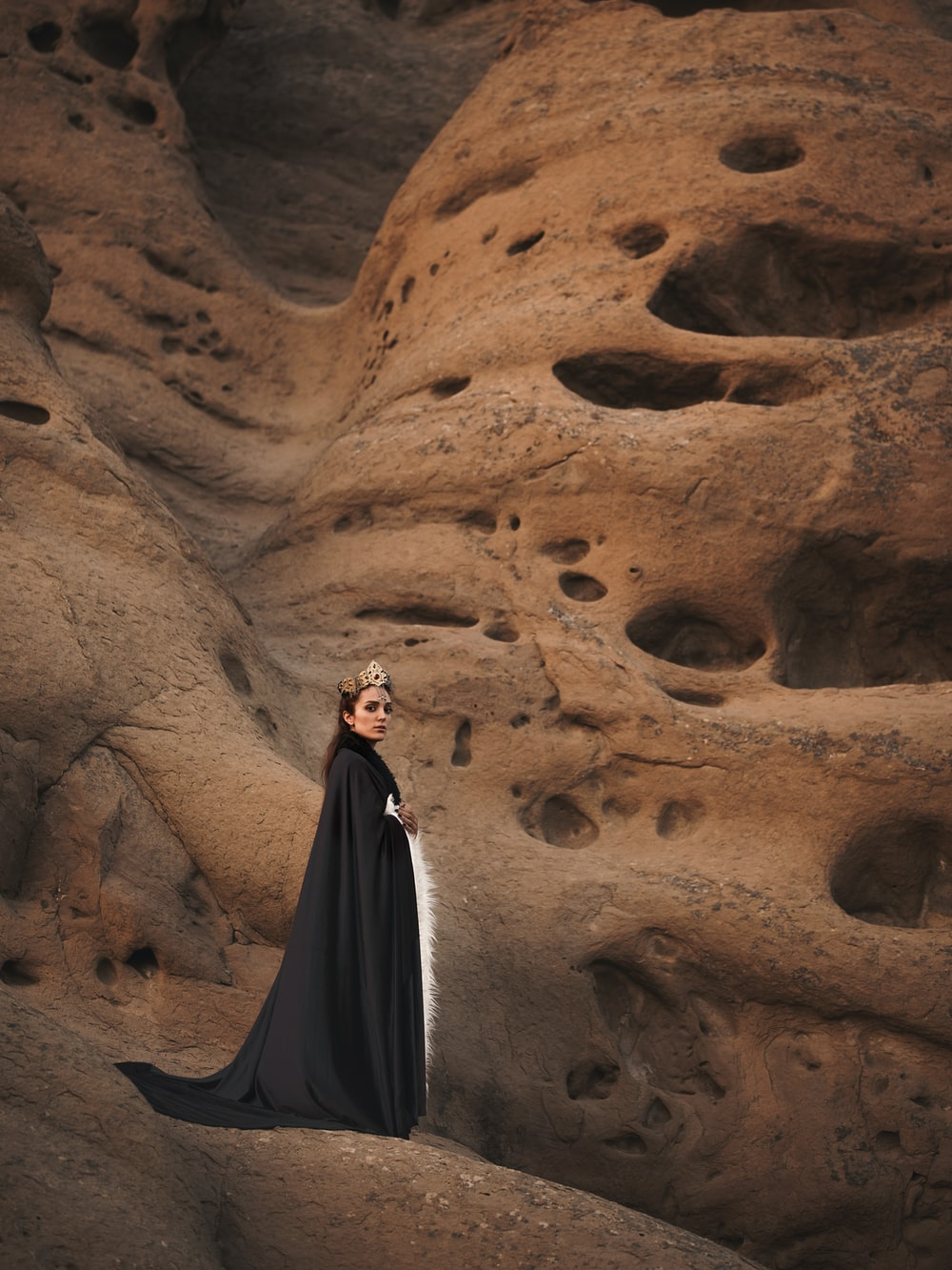 woman in black cape standing on brown mountain