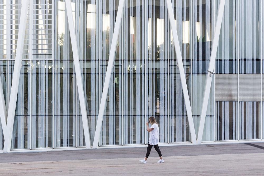 woman walking beside white painted building taken at daytime