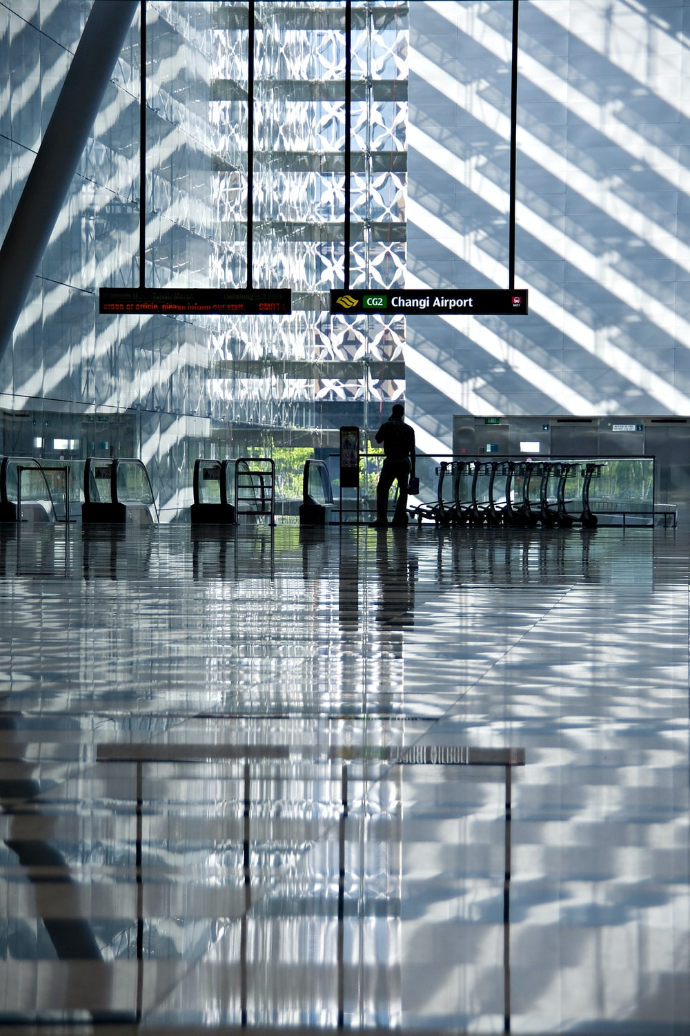 silhouette of man holding bag in inside of airport station during daytime