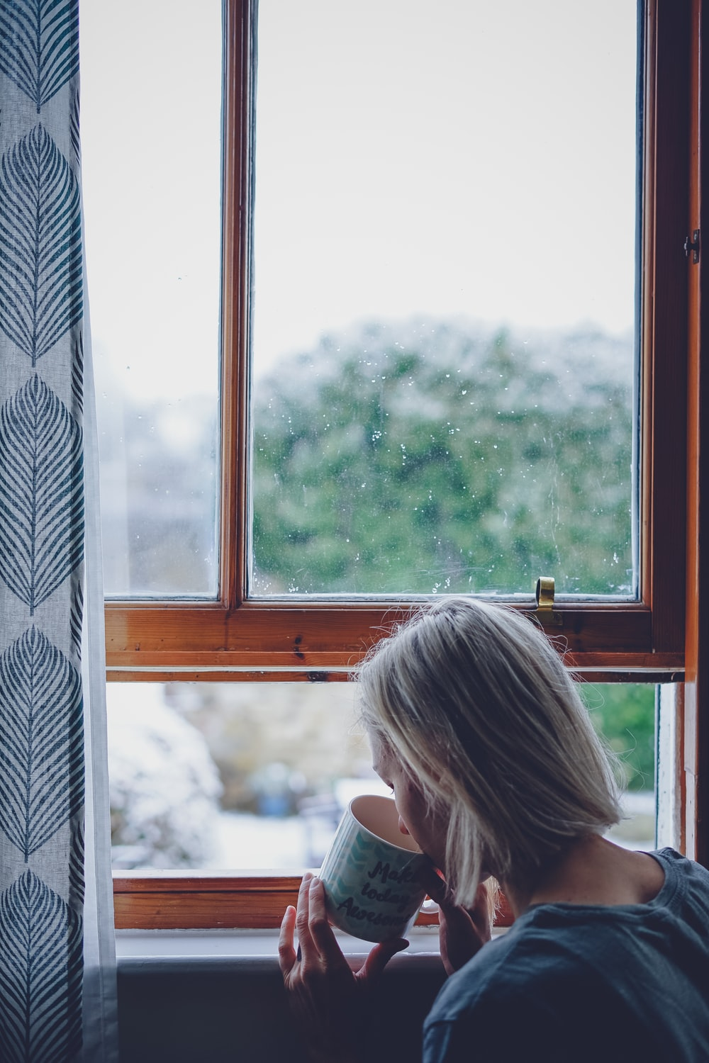 woman drinking in front of window at daytime