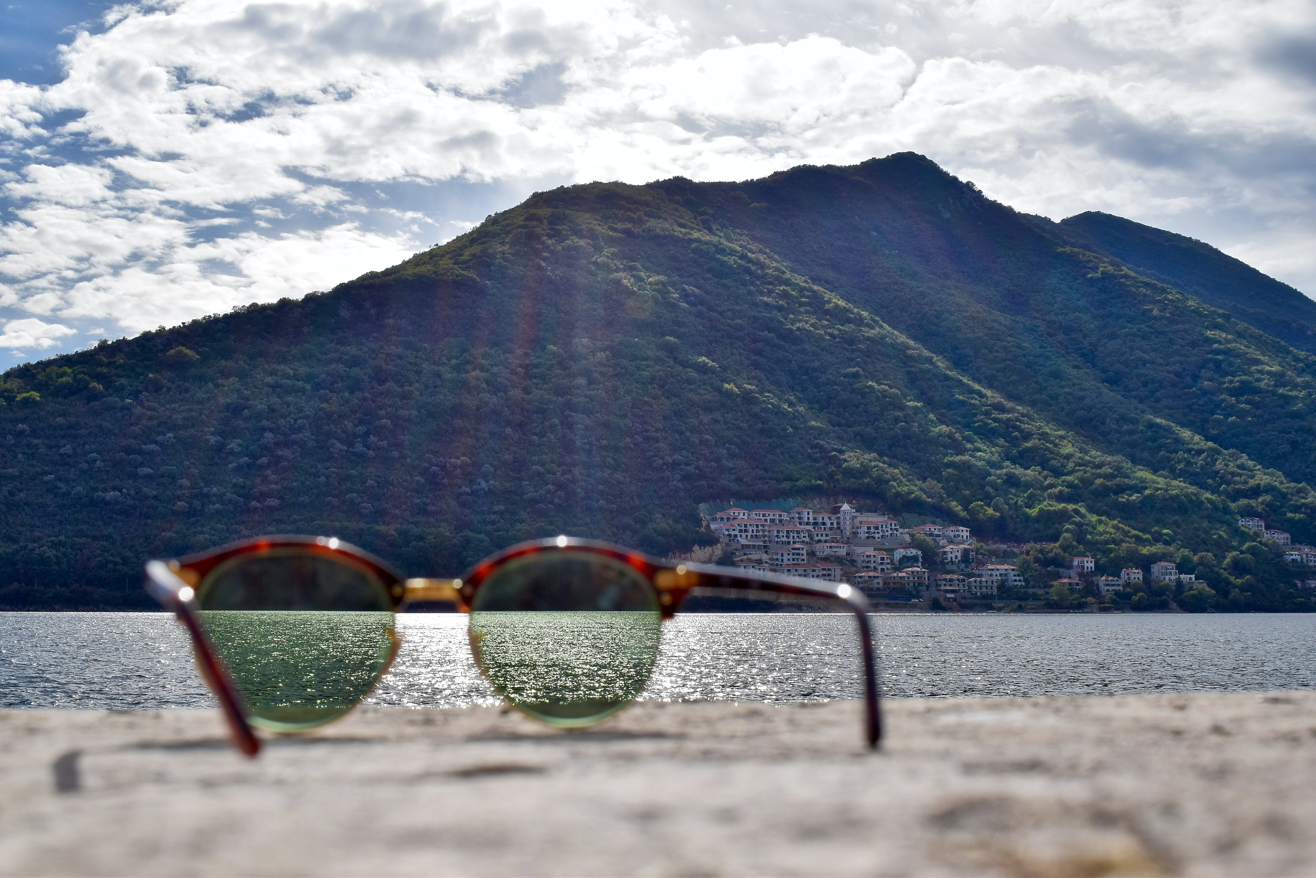gold-colored framed sunglasses facing green mountain at daytime