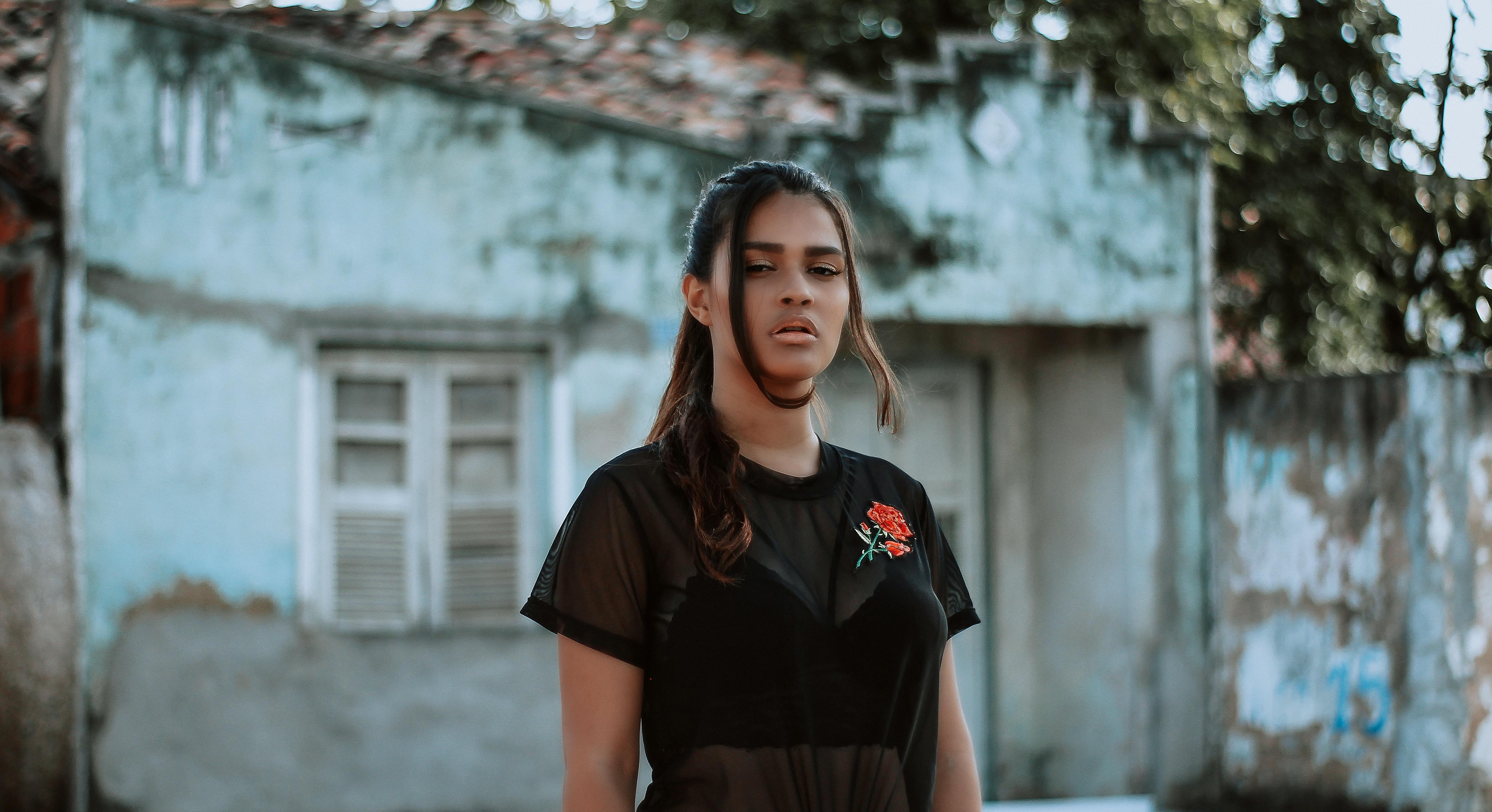 woman wearing black short-sleeved dress near house