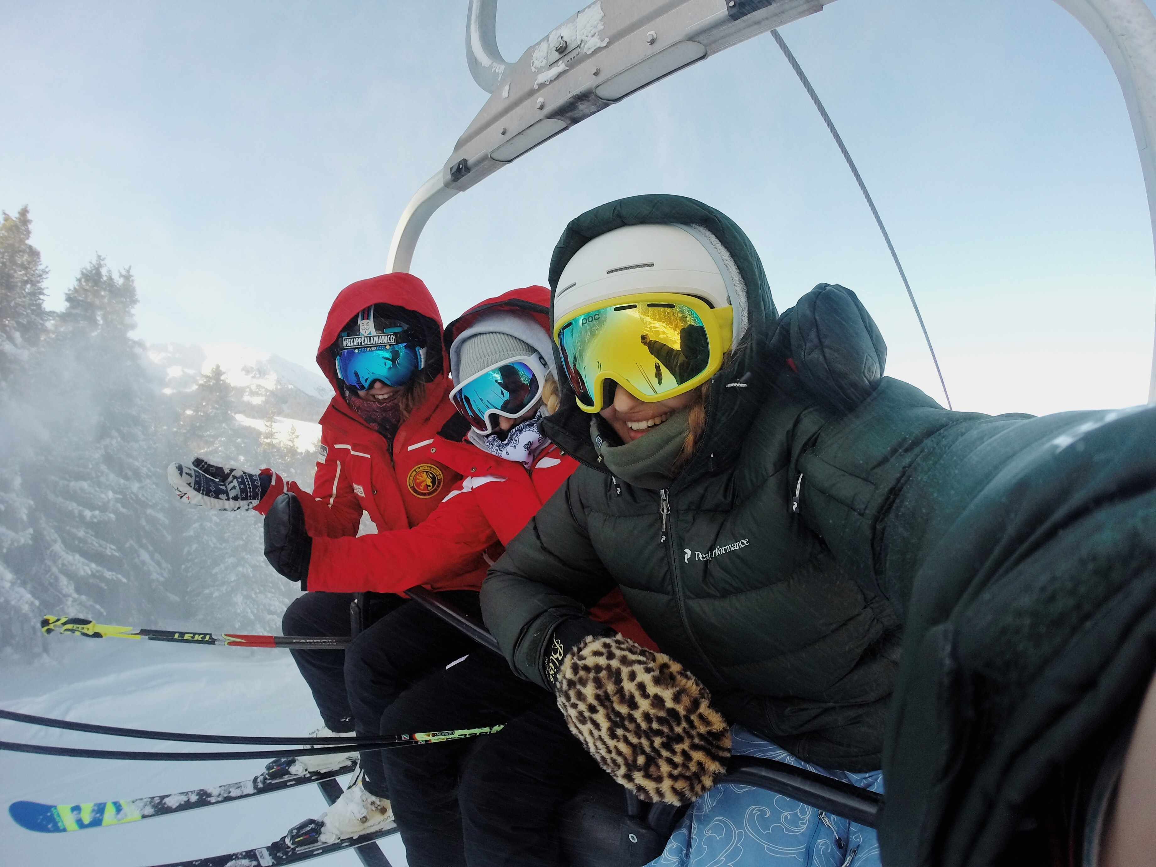 three person wearing ski gear riding cable car